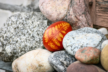 Beautiful red colored Easter egg between pebbles