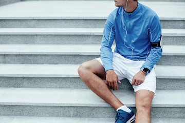 Tired male athlete sitting on the stairs, armband with mobile phone and earphones with music for training