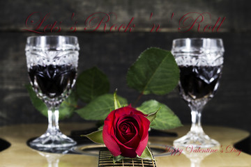 Red Rose and Wine Glasses Resting On Acoustic Guitar With Valentine's Day Concept