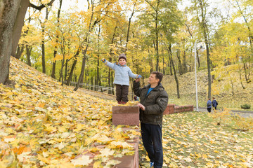 Dad and son in the park in autumn