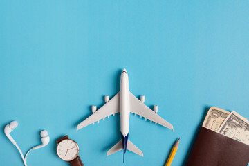 Preparation for Traveling concept, watch, airplane, money, passport, pencils, book, on blue background with copy space.