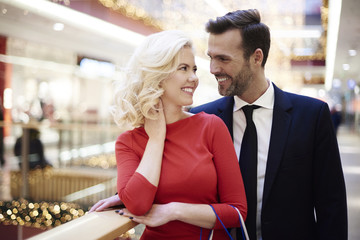 Cheerful couple over shopping in the mall