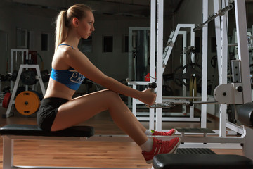 Attractive young fitness model in black-blue sportswear works out on training apparatus in fitness center