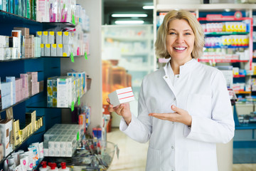 Elderly pharmacist posing in pharmacy