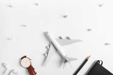 Preparation for Traveling concept, watch, airplane, pencils, book, earphone, push pin, on white background with copy space.