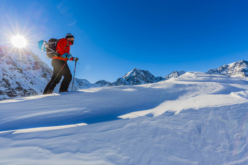 Hiker in winter mountains snowshoeing climbing to the top in sun