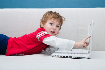 Little boy using laptop at home.