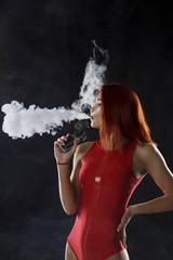 Young beautiful redhead woman vaping e - cigarette.