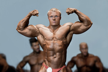 Athlete's double bicep pose. Bodybuilder flexing biceps on stage. Posing in front of competitors. Challenge is accepted.