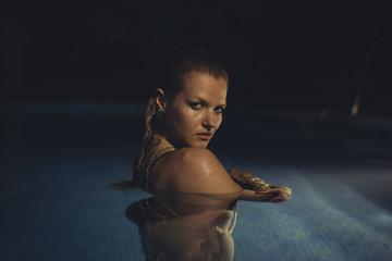 Blonde in pool at night in summer, summer scene in Spain, relaxa
