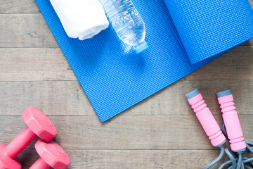 Flat lay of red dumbbells and sport equipment on wood background