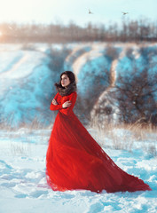 Beautiful brunette girl in a long scarlet outfit