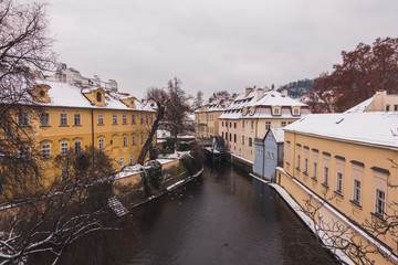 Water canal near Charles Bridge and snow in Prague
