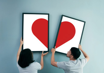 Asian couple holding heat in picture frames.