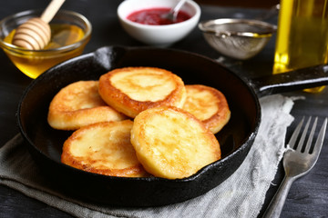 Fried cheesecakes in frying pan