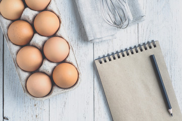 Eggs and ingredients for baking on a light wooden table. Top vie