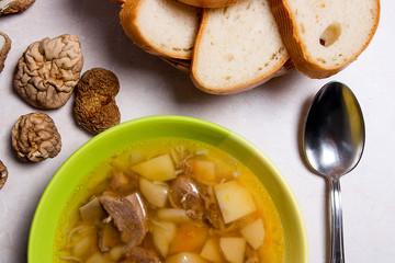 Mushroom soup in green plate with metal spoon, dried wild mushro