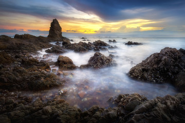 Seascape of sea with dramatic wave and rock in sunset. Wall mural