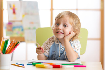 Smiling kid having an idea while drawing in nursery room