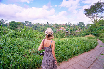 Tourism and travel. Young woman in hat with camera walking on path, enjoying beautiful view.