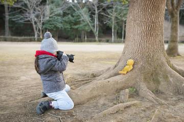 熊の縫い包みの写真を撮る女の子