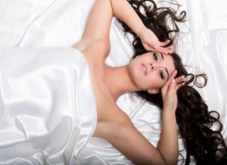 pretty female in peignoir sleeping on bed under silk sheets