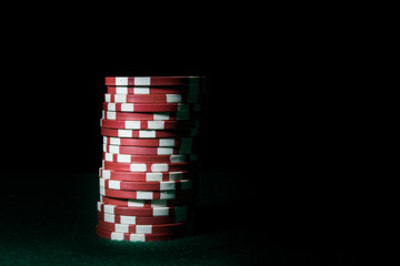 Stack of red poker chips on a dark background
