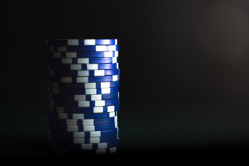 Stack of blue poker chips on a dark background