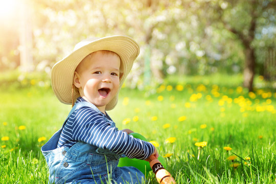 Baby boy sitting on the grass with dandelion flowers in the garden
