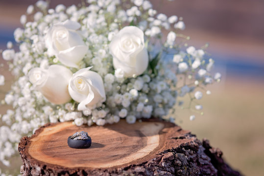 Wedding and engagement rings on wooden stump with white roses