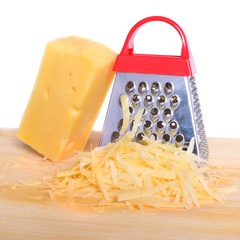 Bar cheese grater and grated cheese on cutting board isolated