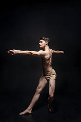 Graceful male dancer acting in the black studio