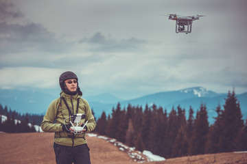 Young man in green jacket operating a drone using a remote controller. Ski resort in the background, winter landscape with pine tree forest and mountains. Vintage toned image. Bukovel, Carpathians