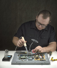 a man at table with a soldering.
