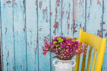 Bouquet of flowers in vintage vase sitting on yellow chair