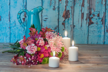 Flowers with an old pitcher and candles