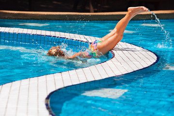 Funny girl swimming and diving in blue pool with fun - jumping deep down underwater with splashes. Family lifestyle, children water sports activity and swimming lesson on summer holiday.