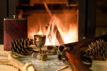 Knife Compass and map lie by the fire. In a fireplace fire burns.