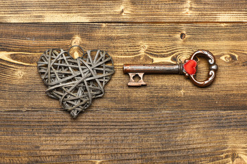 silver heart and metallic key on wood as valentines decoration