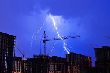 Wall Murals Storm Lightning storm crane weather industrial city building construction night flash