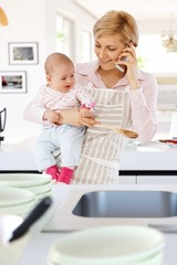Housewife in kitchen with baby and phone in hand