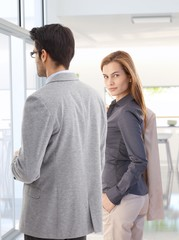 Confident businesswoman with colleague at office