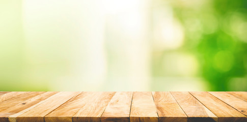 Empty wood table top on blur abstract green garden from window
