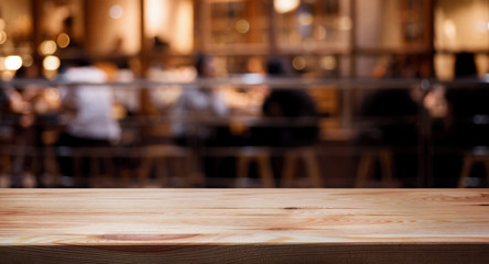Wood table top on blurred of cafe ( restaurant ) with people background.