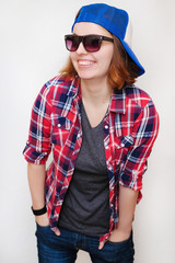 Hipster girl with hair in a red plaid shirt, gray shirt, blue jeans, dark sunglasses, blue cap, a black bracelet on a isolated white background smiling and holding hands in pockets. Closeup portrait.