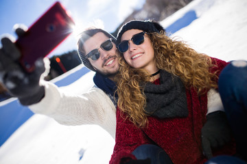 Happy couple taking selfie by smartphone over winter background.