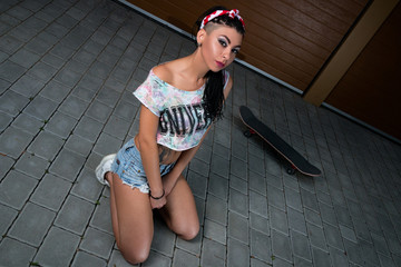 Stylish and sexy girl in erotic shorts with skateboard