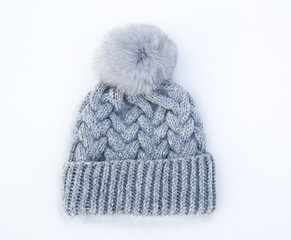 Gray knitted woolen hat with fur pompom