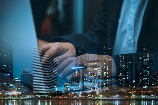 Double exposure of businessman  using laptop and city in busines