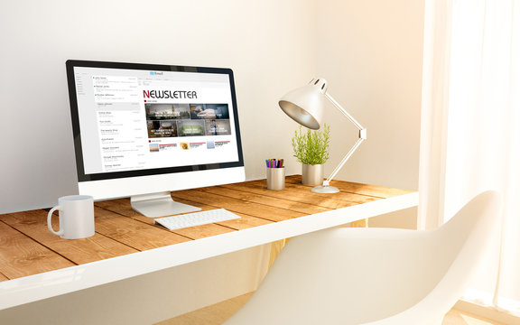 minimalist workplace with newsletter computer